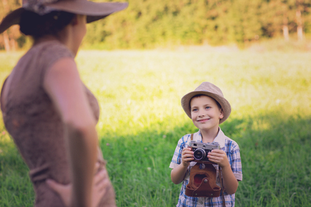 handsome little boy with retro camera and girl model Stock Photo