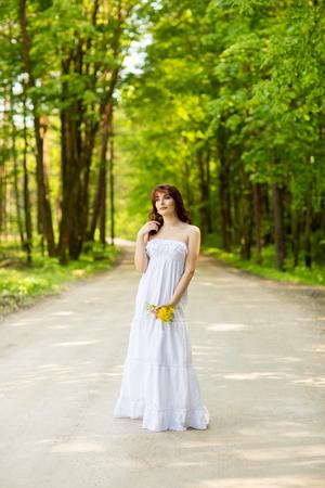 beautiful girl with dandelion flowers on forest road Standard-Bild