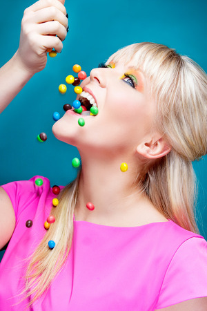 beautiful blond girl with many colorful candies Stock Photo