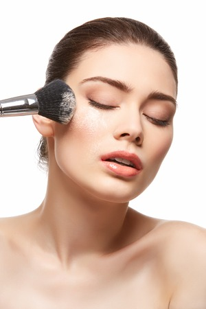girl applying powder on face isolated on white