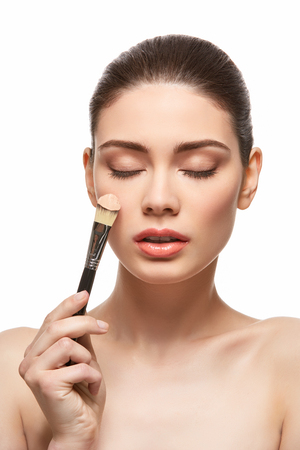 girl applying foundation on face isolated on white Stock Photo