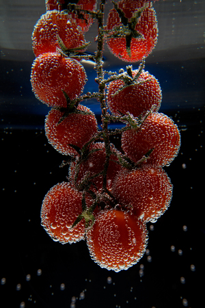 cherry tomatoes covered in bubbles in water