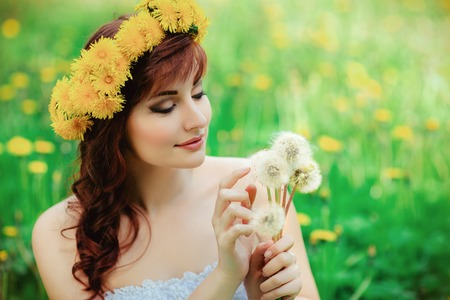 beautiful girl with dandelion flowers in green field