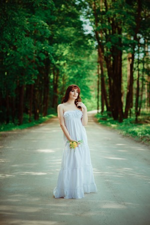 beautiful girl with dandelion flowers on forest road Stock Photo