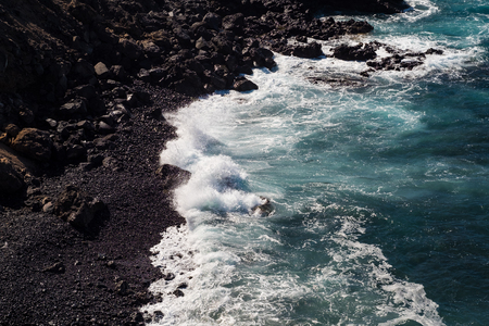 beautiful view on ocean water and black lava sand. outdoor shot on tenerife island. copy space.