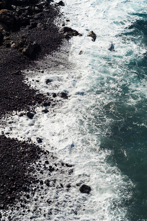 beautiful view on ocean water and black lava sand Stock Photo