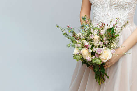 beautiful bride in wedding gown holding lush bridal bouquet. studio shot on light background.