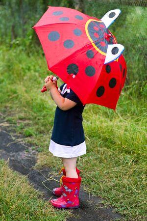lloviendo: La niña con un paraguas y botas de goma Foto de archivo