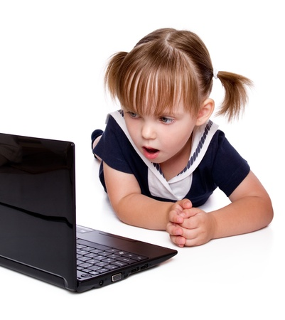 The surprised little girl looks in a laptop photo