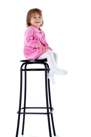 The little girl sits on a high chair. Isolated on a white background Stock Photo - 11411187