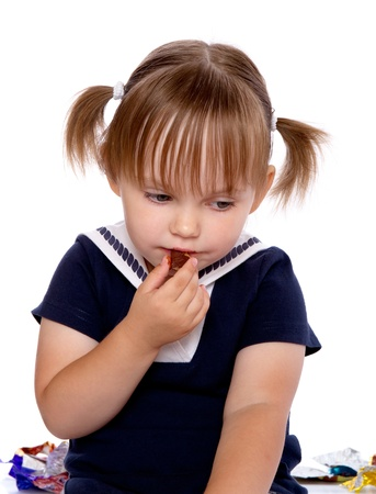 cuddly baby: The little girl eats a chocolate. Isolated on a white background