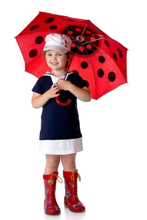 The little girl with an umbrella and in rubber boots. Isolated on a white background photo