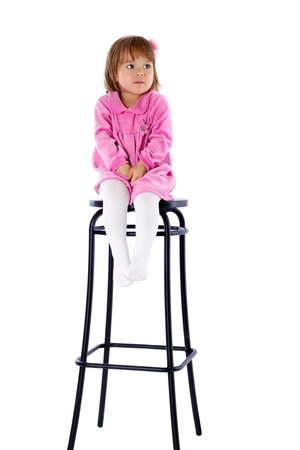 sits on a chair: The little girl sits on a high chair. Isolated on a white background Stock Photo