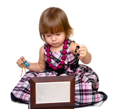 The little girl opens a box with a beads photo