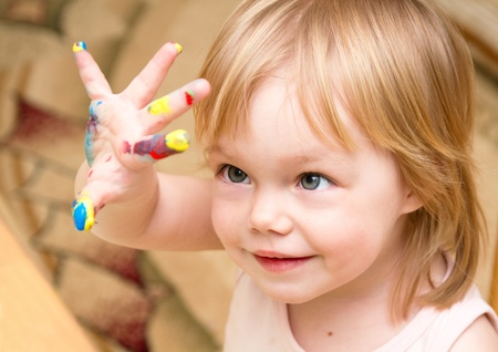 child finger: Smiling child looks at the color hand Stock Photo
