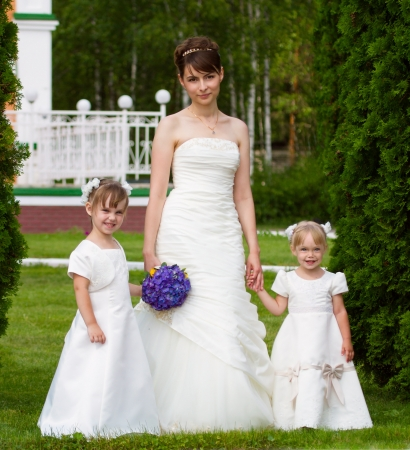 Bride costs with little girls in elegant dresses photo