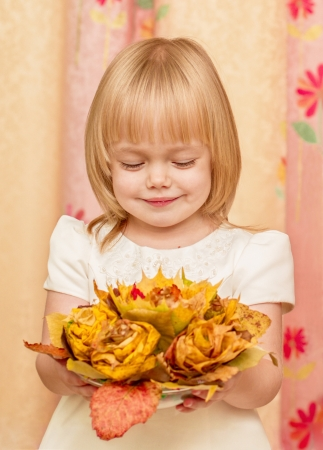 The little girl looks at the bouquet of autumn leaves photo