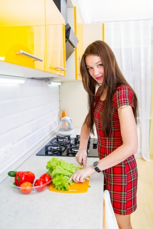 One happy young woman in the kitchen preparing a salad from vegetables photo