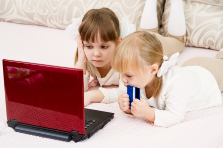 finance girl: Two little girls are with a laptop and a credit card