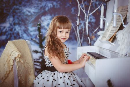 little girl playing piano Christmas in the winter forest photo