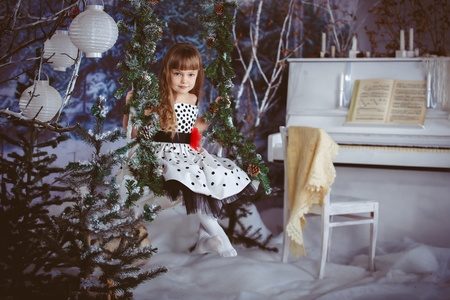 little girl in beautiful dress sitting on a swing in the Christmas winter forest photo