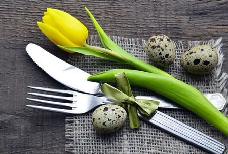 huevos de codorniz: Easter table setting with spring yellow tulip, quail eggs and cutlery on old wooden background with copy space.Spring table setting.Easter decoration.Happy Easter concept.Selective focus.