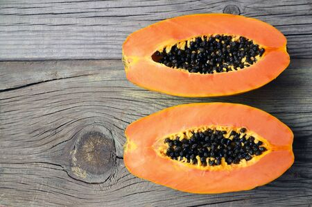 Fresh ripe organic papaya tropical fruit cut in half on old wooden background. Healthy eating, diet or vegan food concept. Selective focus. Reklamní fotografie - 137799741