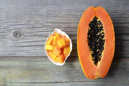 Fresh ripe organic papaya tropical fruit cut in half on old wooden background. Healthy eating, diet or vegan food concept. Selective focus. Reklamní fotografie