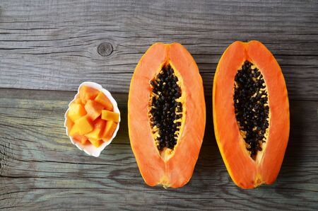 Fresh ripe organic papaya tropical fruit cut in half on old wooden background. Healthy eating, diet or vegan food concept. Selective focus. Reklamní fotografie - 137799489