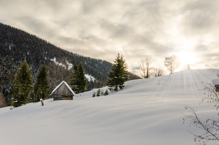 cloudscapes: House on a hillside covered with snow and green trees on the sides, with hhory Blue Christmas forest in the background Winter landscape. Stock Photo