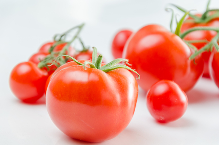 Composition of small cherry and large tomato. Isolated Stock Photo