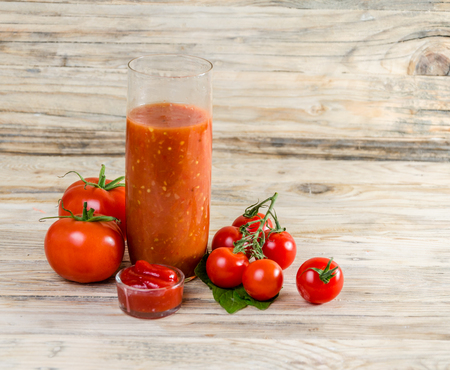 cooking oil: Composition from a tomato, ketchup and a glass of juice on a wooden background.