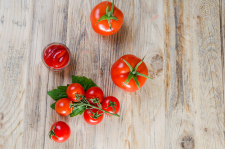 cooking oil: Composition from a tomato and ketchup on a wooden background.