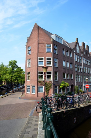 corner house: Corner house and many bikes on canal in Amsterdam, Holland  Stock Photo