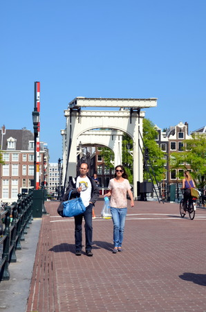 Tourists walk across the Skinny bridge  Magere brug  over the Amstel river  in Amsterdam, Holland