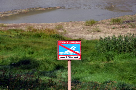 no swimming sign:  No swimming  sign on the bank of the river