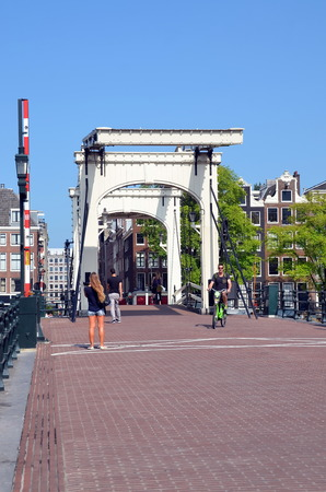 Tourists walk across the Skinny bridge (Magere brug) over the Amstel river  in Amsterdam, Holland