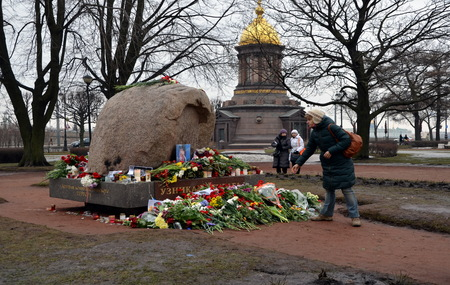 boris: A  girl lays flowers in memory of Boris Nemtsov at Solovetsky stone, monument to the victims of GULAG