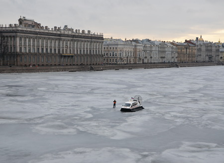 situations: Employee of the Ministry of Emergency Situations stands next to hydroplane on the Neva river. Action in memory of Boris Nemtsov on March 1, 2015