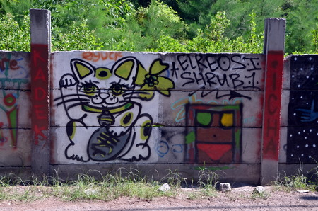 cat island: GILI TRAWANGAN INDONESIA MAY 24 2015  Manekineko Lucky Cat graffiti on the island of Gili Trawangan Indonesia Editorial
