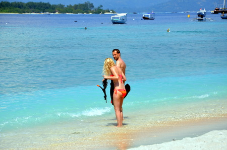 enters: ouple with snorkeling equipment enters the sea. Gili Trawangan, Indonesia