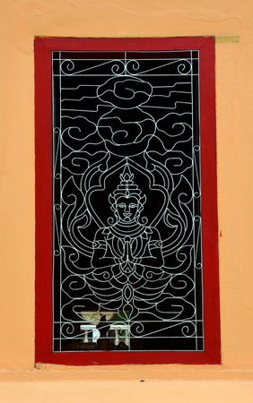 lattice window: Buddha. Openwork lattice window at a Buddhist monastery in Vientiane, Laos