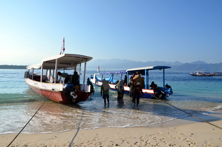 unload: Gili Trawangan, Indonesia. Men unload a boat Editorial