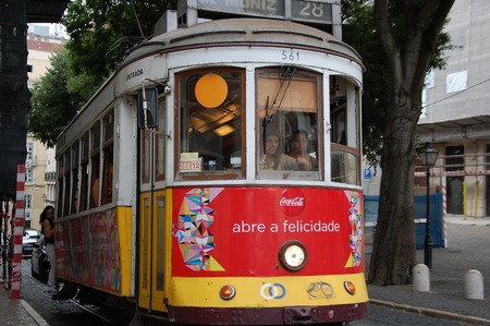 gloria: Girl rides on the running rail of tram in Lisbon, Portugal