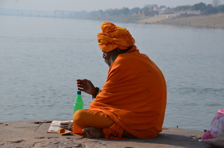 sadhu: A sadhu reads religious book on the banks of the Holy Ganges river Editorial