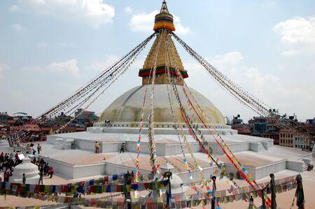 Tourists at Bodnath stupa with Buddha eyes and prayer flags in Kathmandu, Nepal Editorial