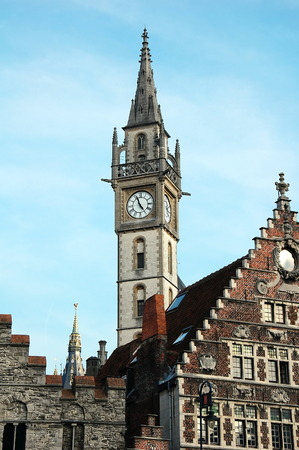 Details of old Post Office building with the clock tower against blue sky in Ghent, Belgium