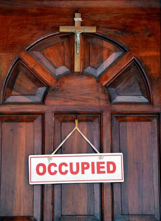 occupied: Old wooden door with a crucifix and doorsign Occupied