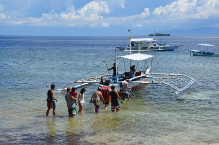 Passengers go through the water on a boat, Moalboal, Philippines, Cebu Island