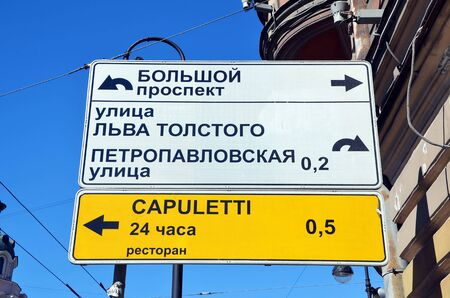 str: St-Petersburg, road  direction sign with restaurant advertising. Translation:  Bolshoy Pr, Leo Tolstoy str, Petropavlovskaya str,  Capuletti  restaurant